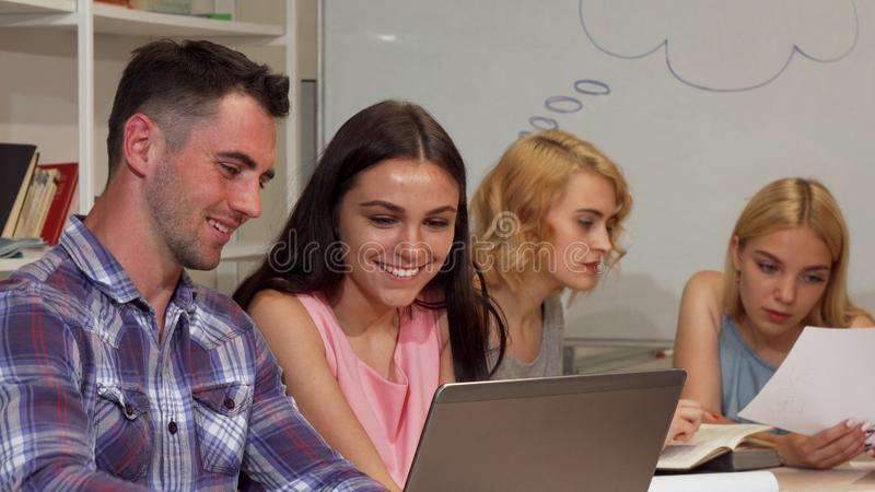 Two young cheerful students discussing their project on the laptop stock photography