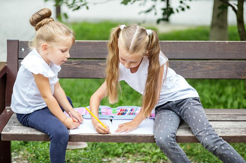 Two young children draw in the school park. The concept of school, friendship, drawing, study, hobby.  royalty free stock photo