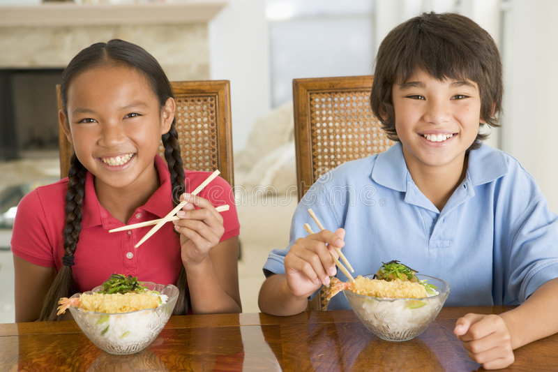 Two young children eating Chinese food stock photo