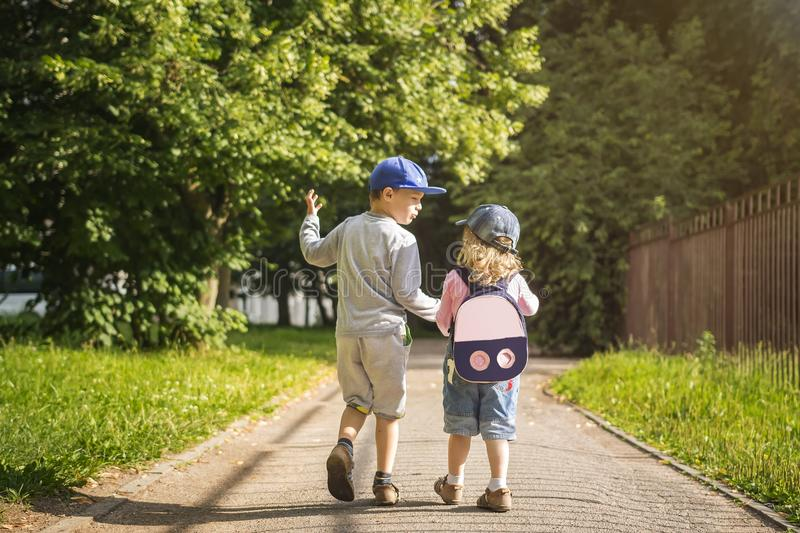 Two young children friends boy and girl hold hands and walk along road in summer green park on sunny afternoon. Child friendship royalty free stock photography