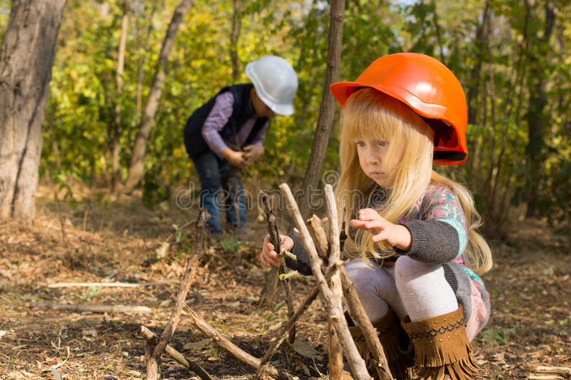 Two young children playing at being builders. Outdoors in the woods as they collect twigs to build a wooden framework in their hardhats with focus to a little stock photo