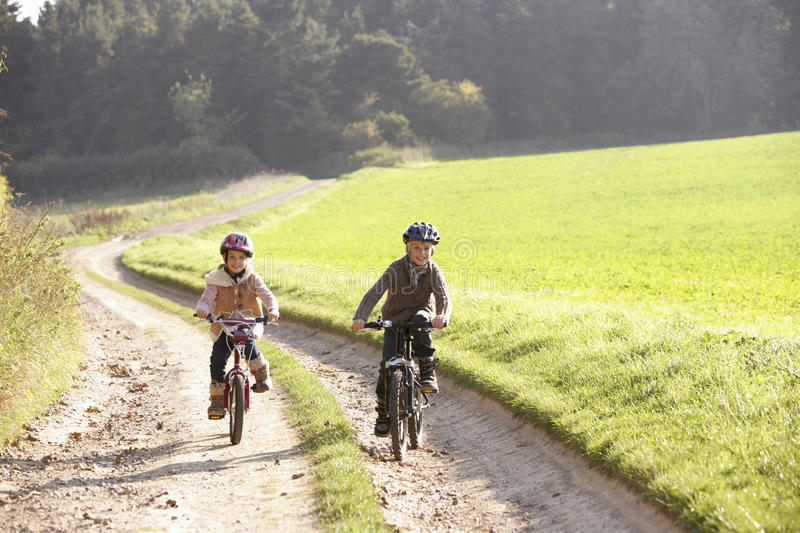 Two young children ride bicycles in park