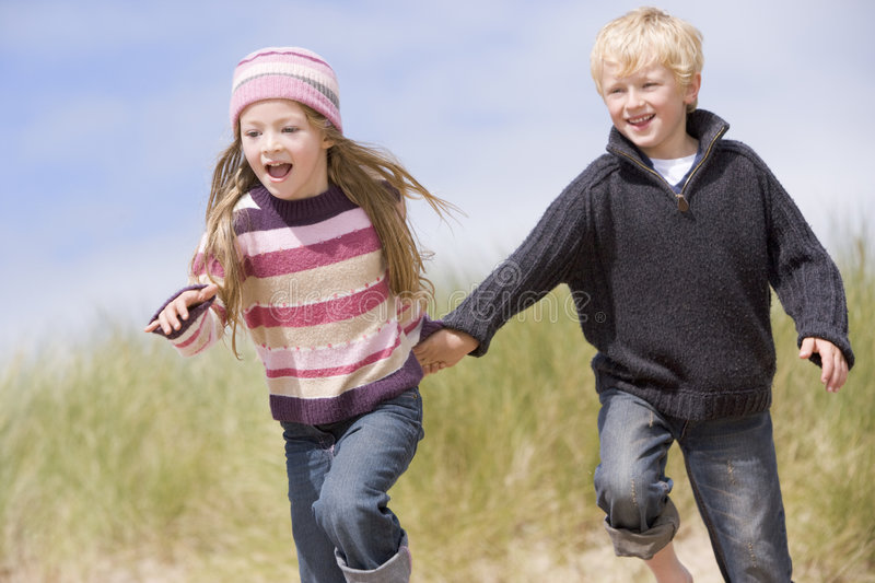 Two young children running on beach holding hands royalty free stock photo