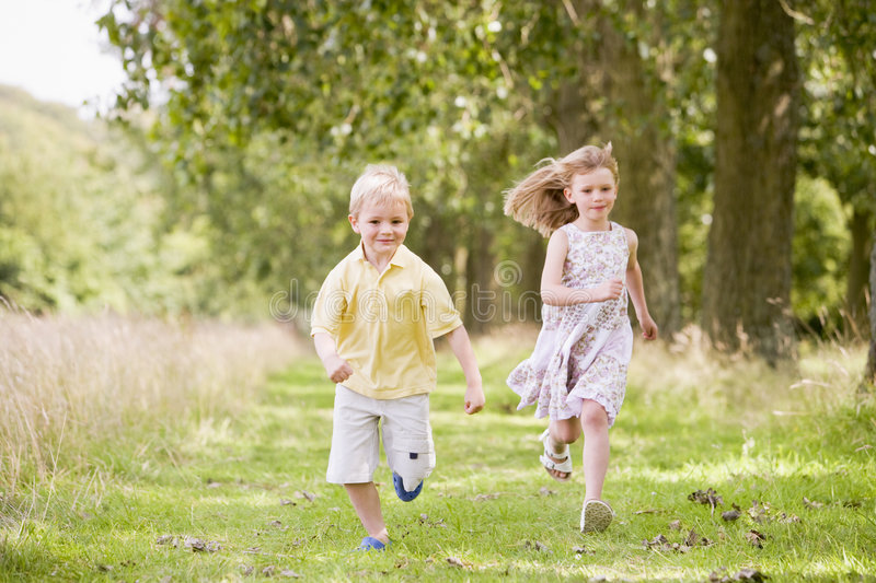 Two young children running on path smiling royalty free stock images
