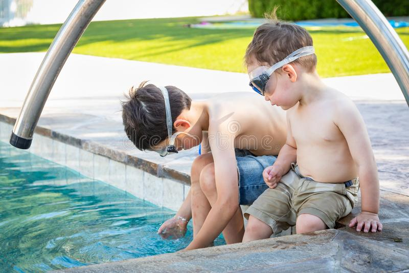 Two Young Chinese Caucasian Brothers By the Pool Wearing Swimming Goggles royalty free stock photo
