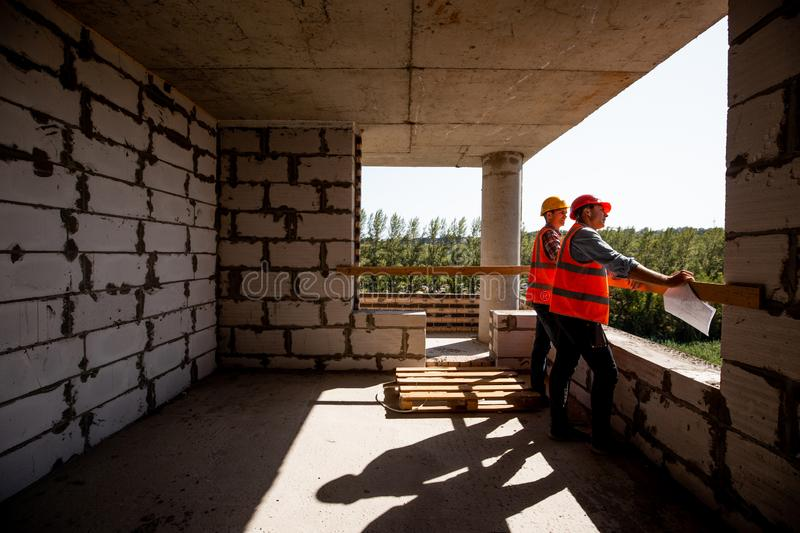Two young civil engineers dressed in orange work vests and helmet stand on the building site inside the building under royalty free stock photography