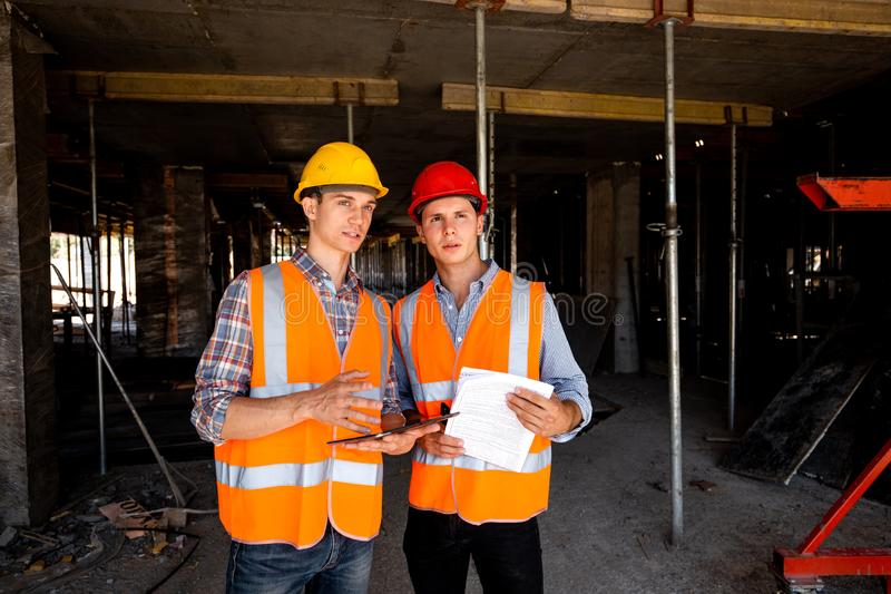 Two young civil engineers dressed in orange work vests and helmets work with tablet and documentation inside the stock image