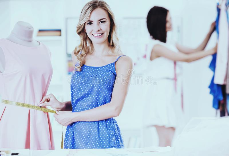 Two Young Clothing Designer Working with Fabric in Sewing Design Showroom. royalty free stock photography