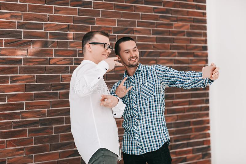 Two young co-workers taking selfies standing in the office. People and technology stock image