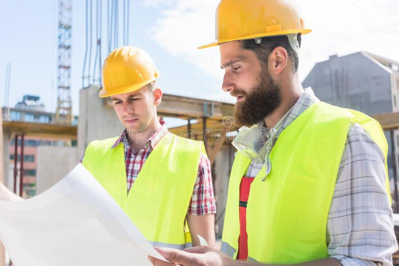 Two young construction workers analyzing together the plan of a royalty free stock image