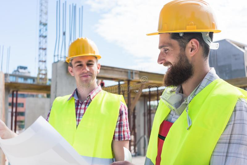 Two young construction workers analyzing together a plan royalty free stock photos