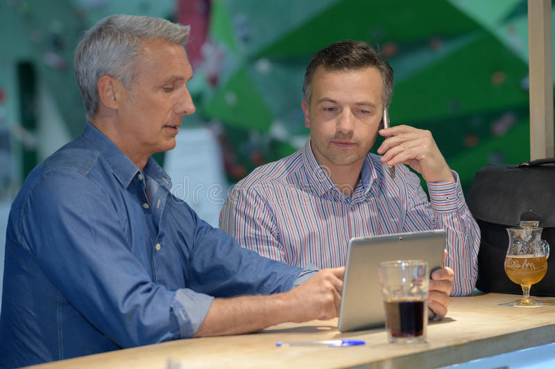 Two young contemporary businessmen working and relaxing at bar royalty free stock photos