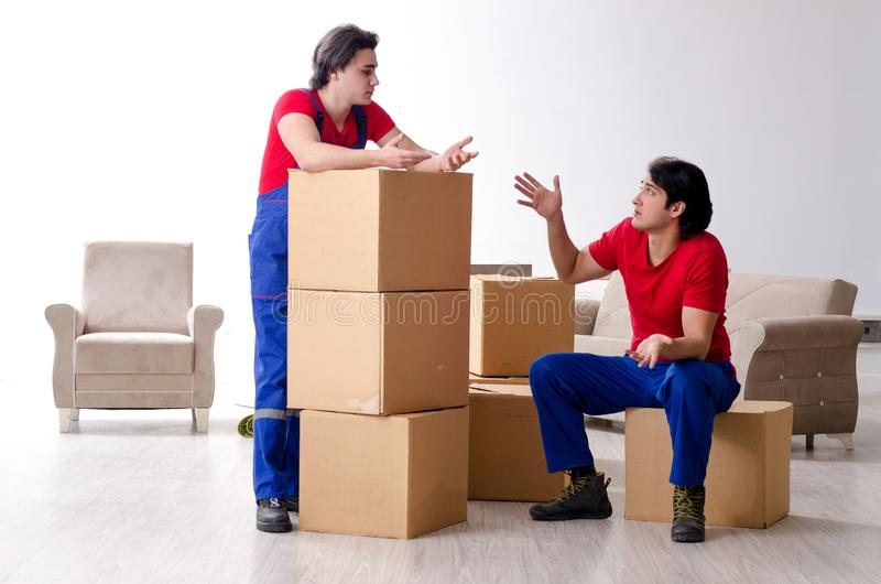 Two young contractor employees moving personal belongings. The two young contractor employees moving personal belongings stock images