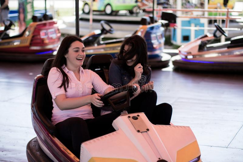 Young women having a bumper car ride. Two young cool women having a fun bumper car ride at the amusement park. Friendship royalty free stock photo