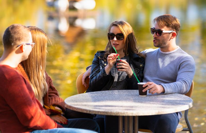 Two young couples enjoying coffee outdoors royalty free stock photo