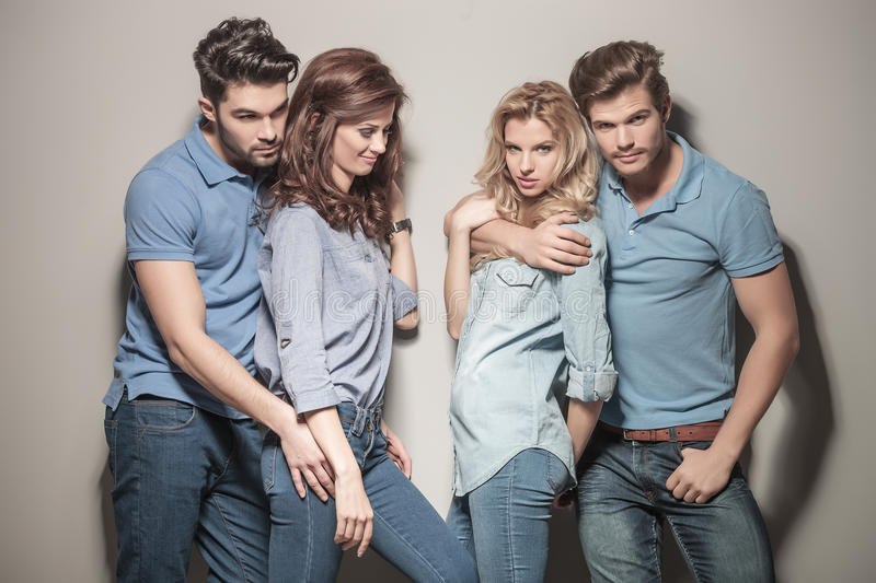 Two young couples of people standing embraced. Two young couples of casual people standing embraced near each other stock images