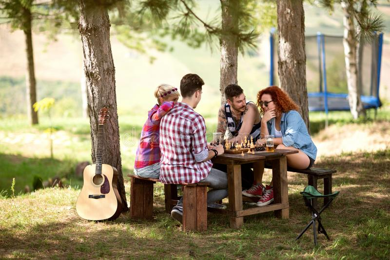 Two young couples plays chess in woods stock photography