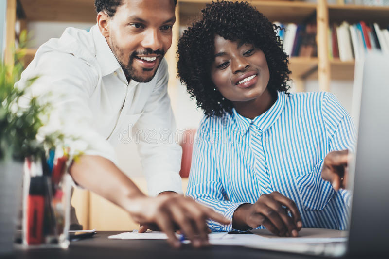 Two young coworkers working together in a modern office.Black business partners discussing new startup project stock photography