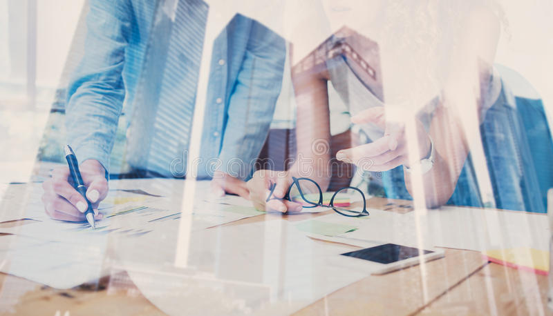 Two young coworkers working on wooden table in modern coworking studio.Double exposure,skyscraper building,blurred. Background.Horizontal stock photos