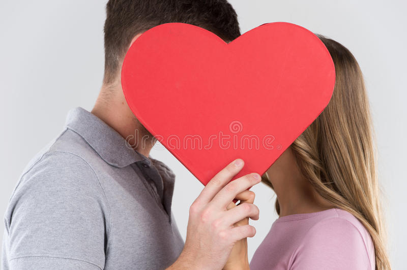Two young dates behind heart with their faces close to one another. stock photo