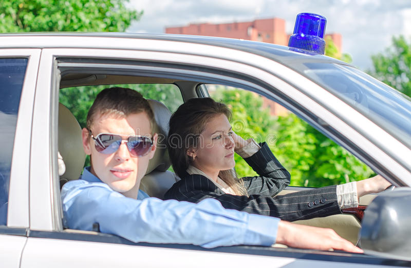 Two young detectives. Driving to crime scene royalty free stock image