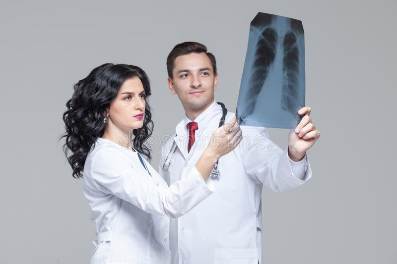 Two young doctors looking at the x-ray picture of lungs.  royalty free stock photography