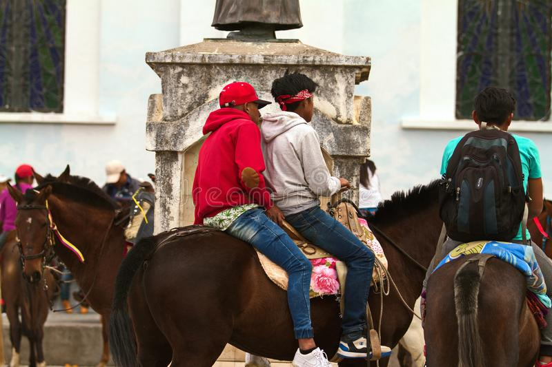 Two boys riding a horse during a celebration in Ecuador royalty free stock photo
