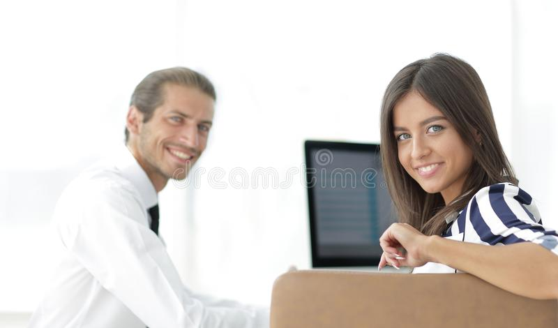 Two young employee sitting behind a Desk. Closeup.two young employee sitting behind a Desk royalty free stock photography