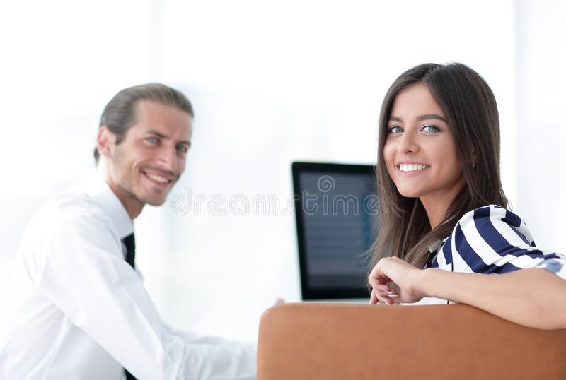 Two young employee sitting behind a Desk. Closeup.two young employee sitting behind a Desk stock photo