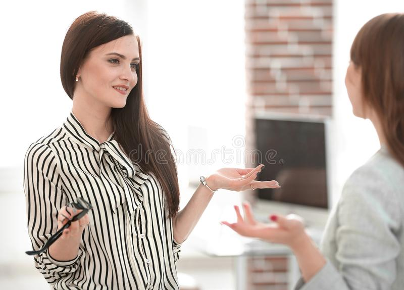 Two young employees are talking in the office. royalty free stock photos