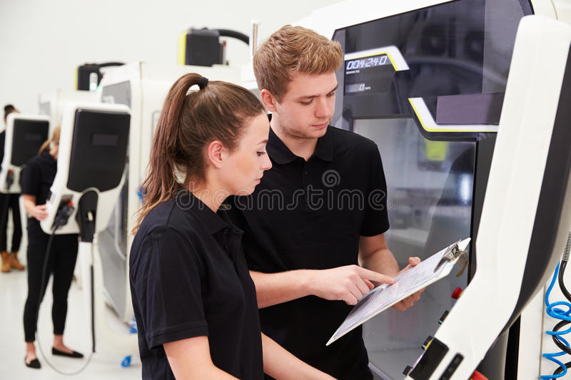 Two Young Engineers Operating CNC Machinery On Factory Floor stock image
