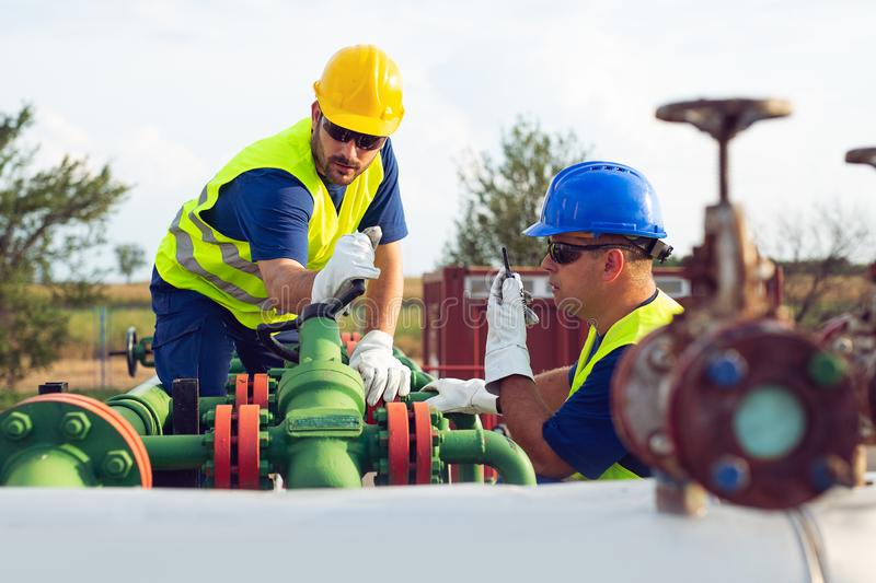 Two engineers working inside oil and gas refinery royalty free stock photo