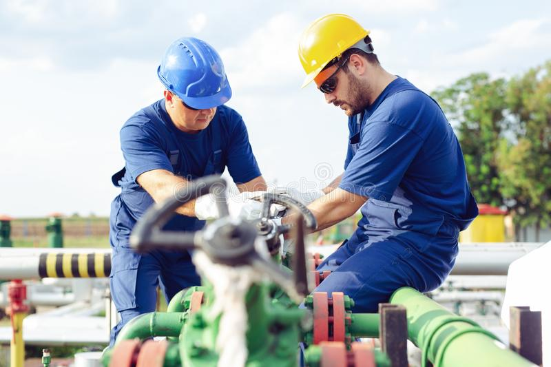 Two engineers working inside oil and gas refinery. Two young engineers working inside oil and gas refinery royalty free stock photography