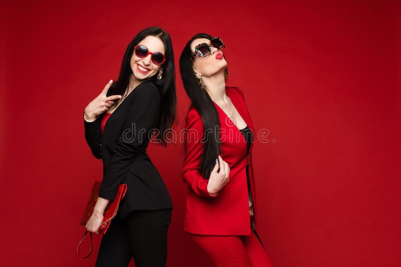 Two young fashion stylish female model in sunglasses smiling posing isolated at red studio stock photos