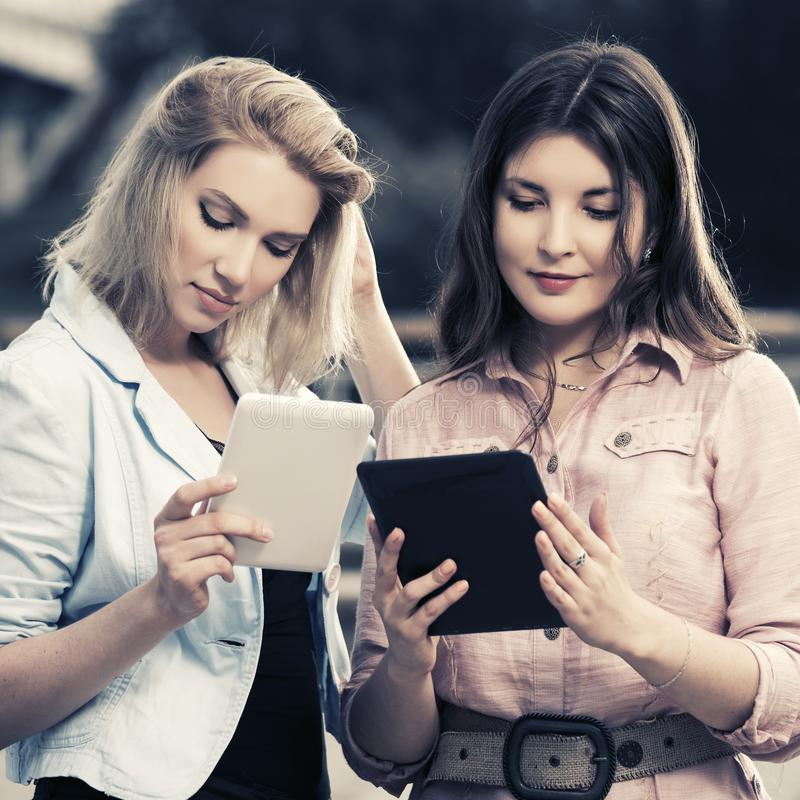 Two young fashion women using tablet computer outdoor stock photo