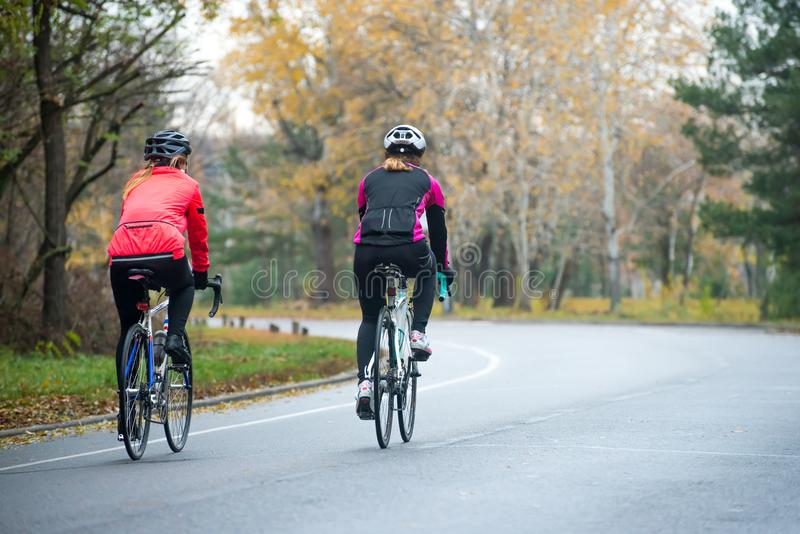 Two Young Female Cyclists Riding Road Bicycles in the Park in the Cold Autumn Morning. Healthy Lifestyle. Two Young Female Cyclists Riding Road Bicycles in the royalty free stock photo