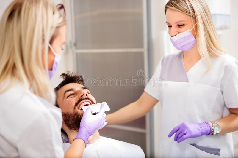 Two young female dentists working in dental clinic. Whitening male patient`s teeth and using tone chart to mach color stock photo