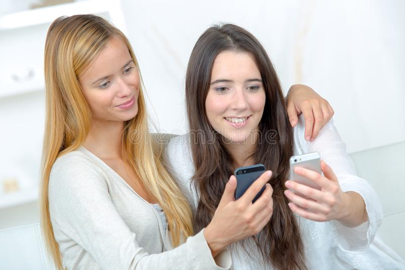Two young female friends check mobile phones stock photos