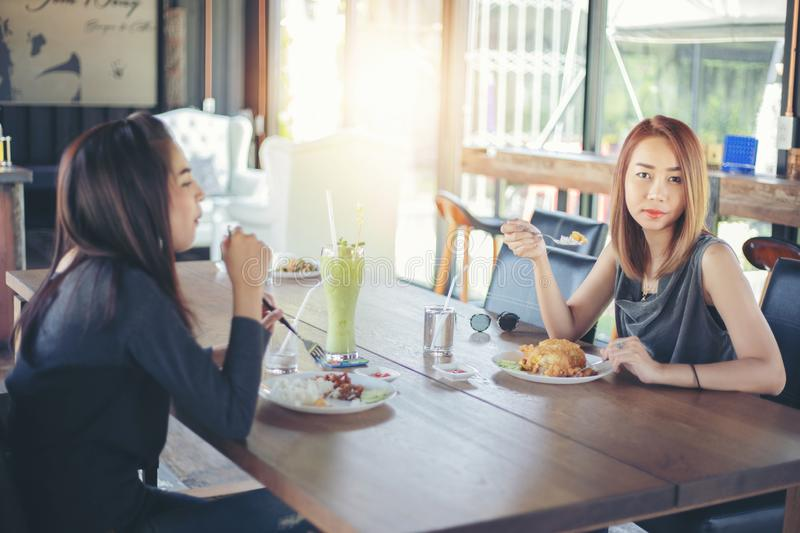 Two young female friends laugh and Having Lunch Together At Rest royalty free stock images