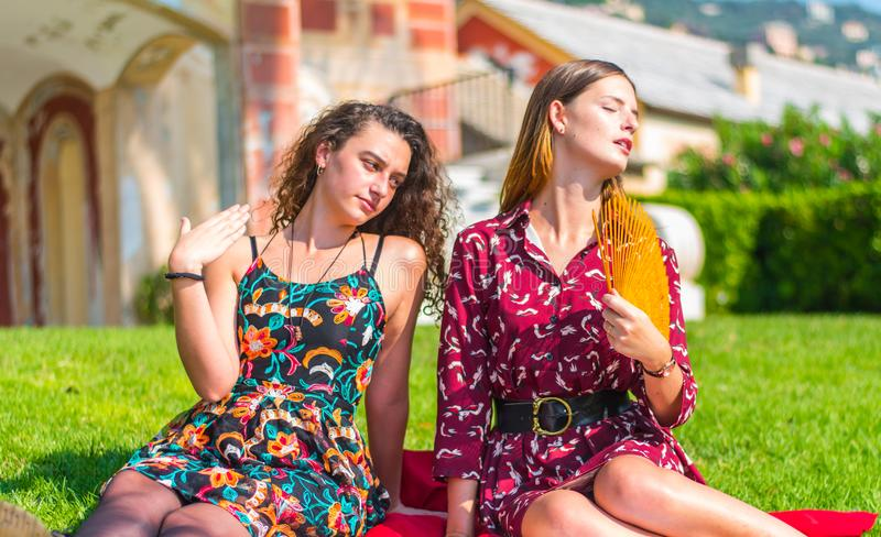 Summer heat in the park. Two young female friends trying to escape the high summer heat and using a fan to cool down royalty free stock photo