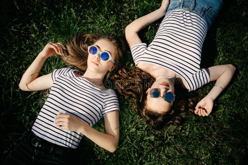 Two young female girl friends in sunglasses laying on the grass in park. Trendy Hipster Best friends Girls Relaxing. Summer stock images