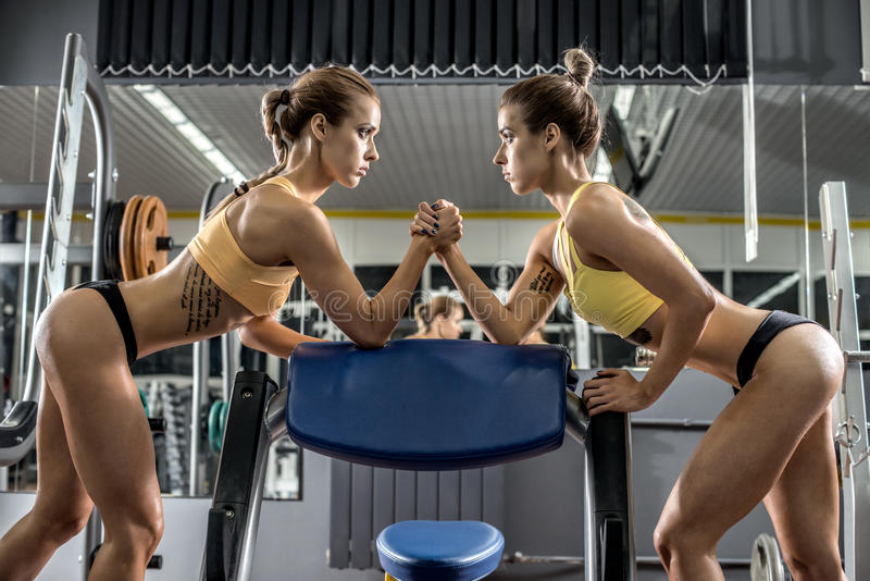 Two young fitness woman, arm wrestling in gym. Horizontal photo royalty free stock photo
