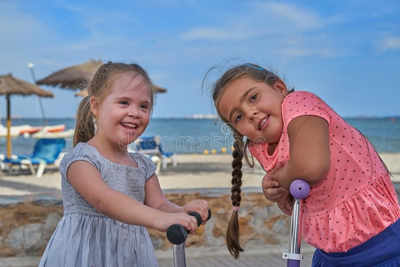 Two Happy Young Girls on Scooters by the Beach royalty free stock image