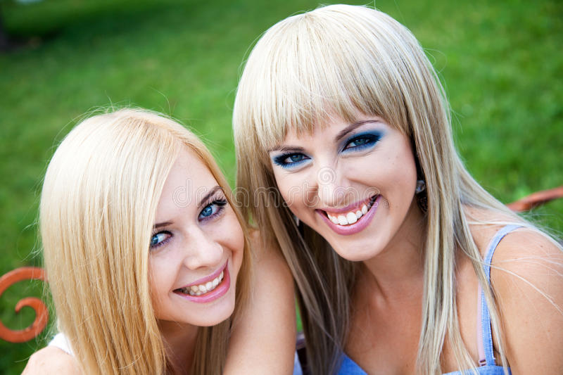 Two young girl friends in a park stock images