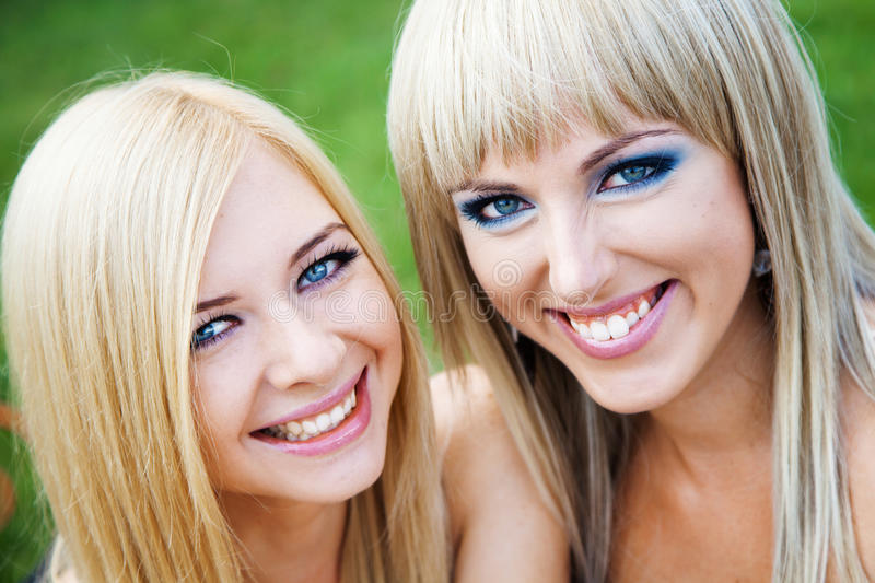 Two young girl friends in a park stock photography