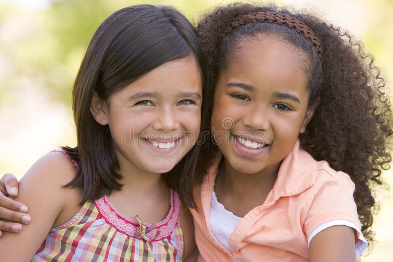 Two young girl friends sitting outdoors royalty free stock photography
