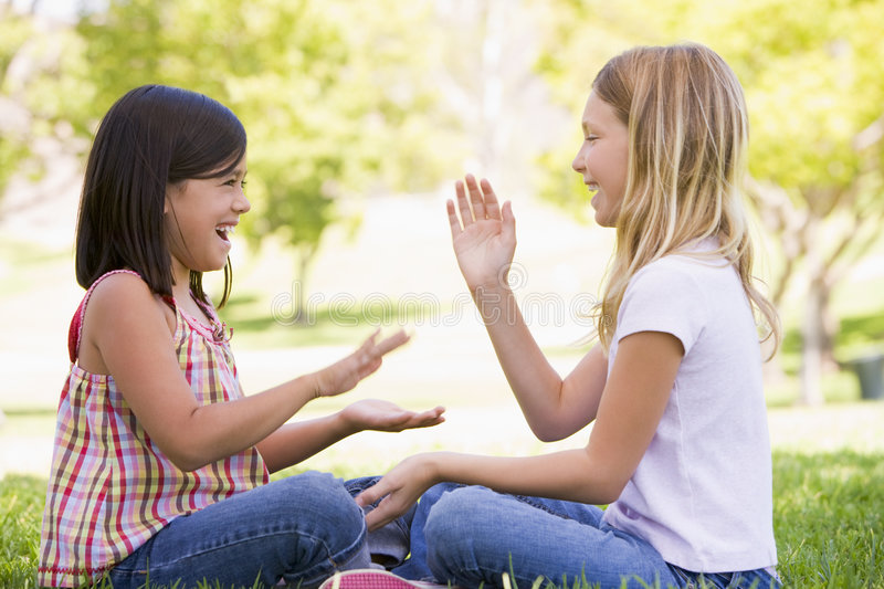 Two young girl friends sitting outdoors playing royalty free stock photo