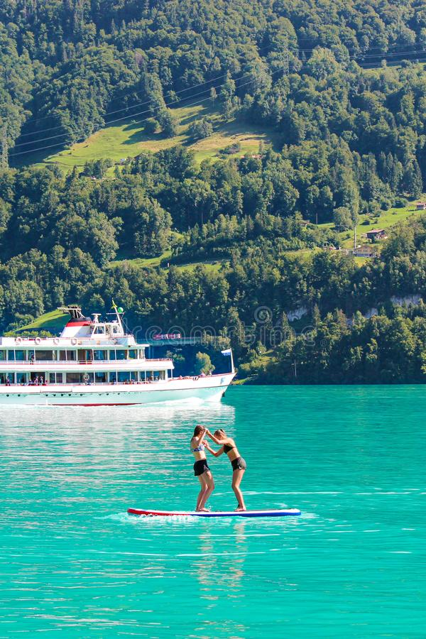 Two young girl friends standing on paddle board on turquoise Lake Brienz in Switzerland. Tourist boat in background. Switzerland stock images