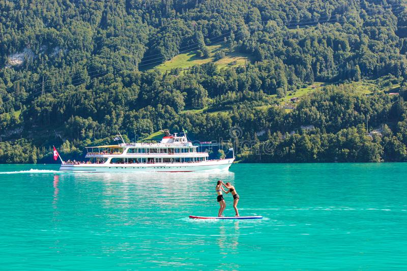Two young girl friends standing on paddleboard on turquoise Lake Brienz in Switzerland. Tourist boat in background. Switzerland stock photos