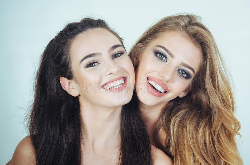 Two young girl friends standing together stock photos